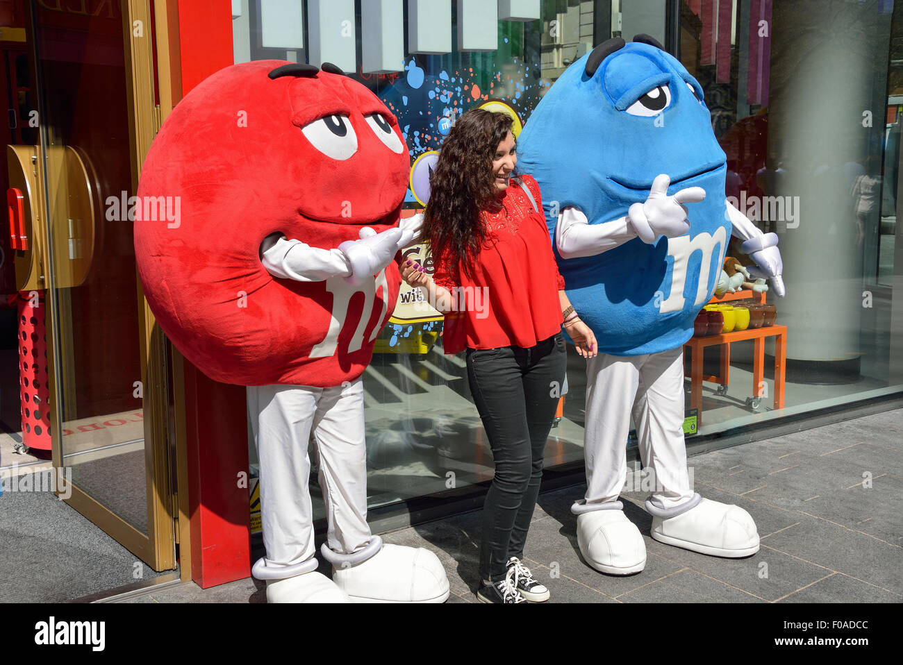 Young woman with characters outside M&M's World, Leicester Square, West End, City of Westminster, London, - Stock Image