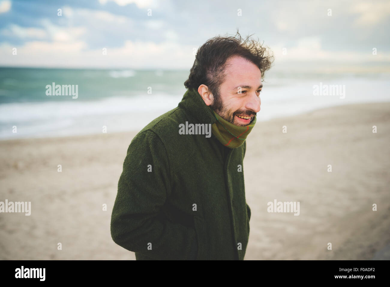 Portrait of mid adult man on windy beach, Sorso, Sassari, Sardinia, Italy - Stock Image