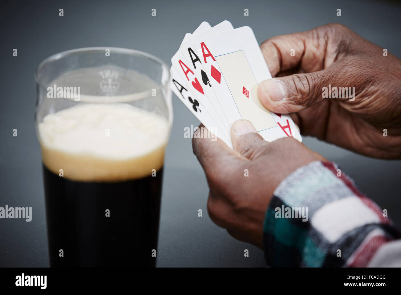 Man holding four ace cards with beer - Stock Image