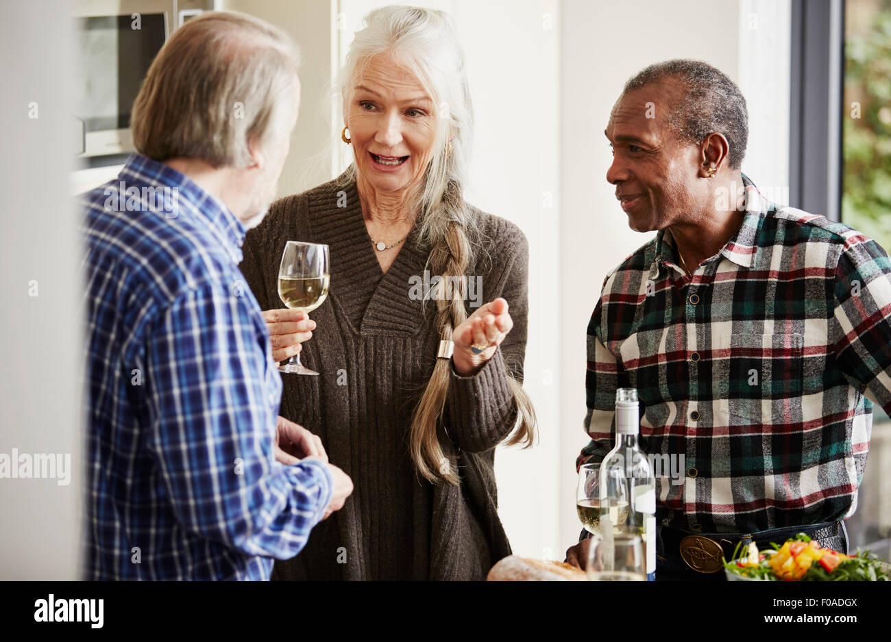 Senior friends talking in kitchen with wine - Stock Image