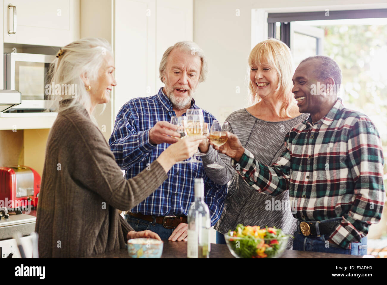 Senior friends toasting with wine in kitchen - Stock Image