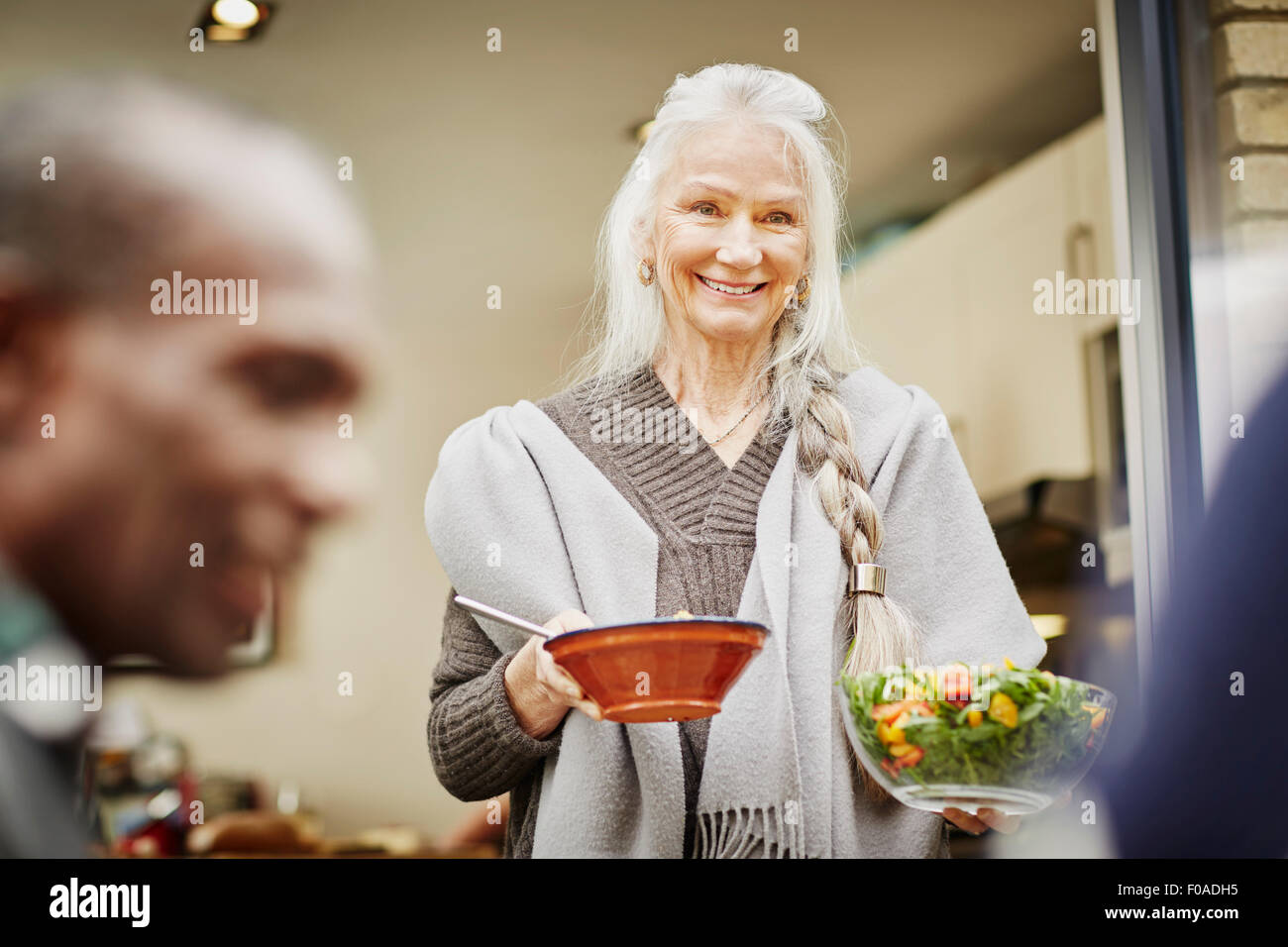 Senior woman carrying bowls of salad outside Stock Photo