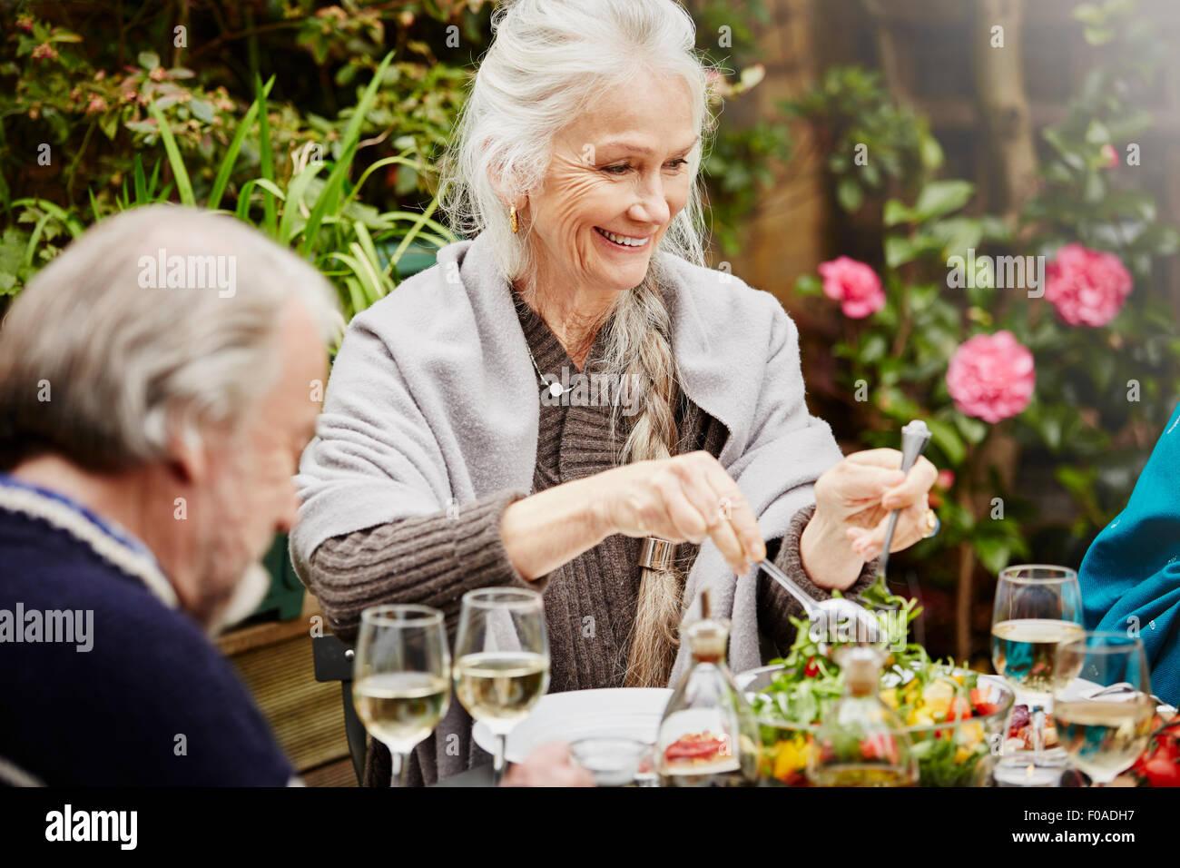 Senior friends eating meal in garden - Stock Image