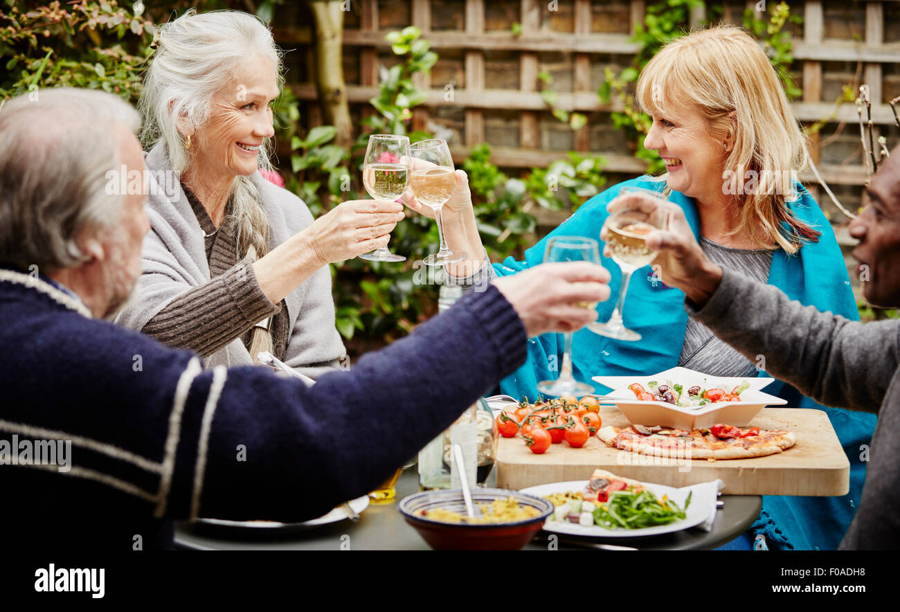 Senior friends making a toast during meal in garden - Stock Image