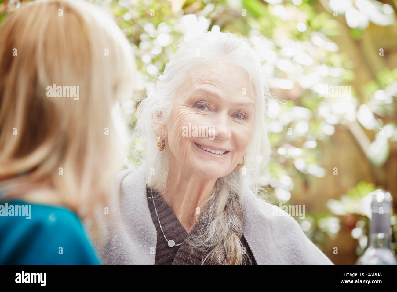 Senior woman with grey hair in garden, portrait - Stock Image