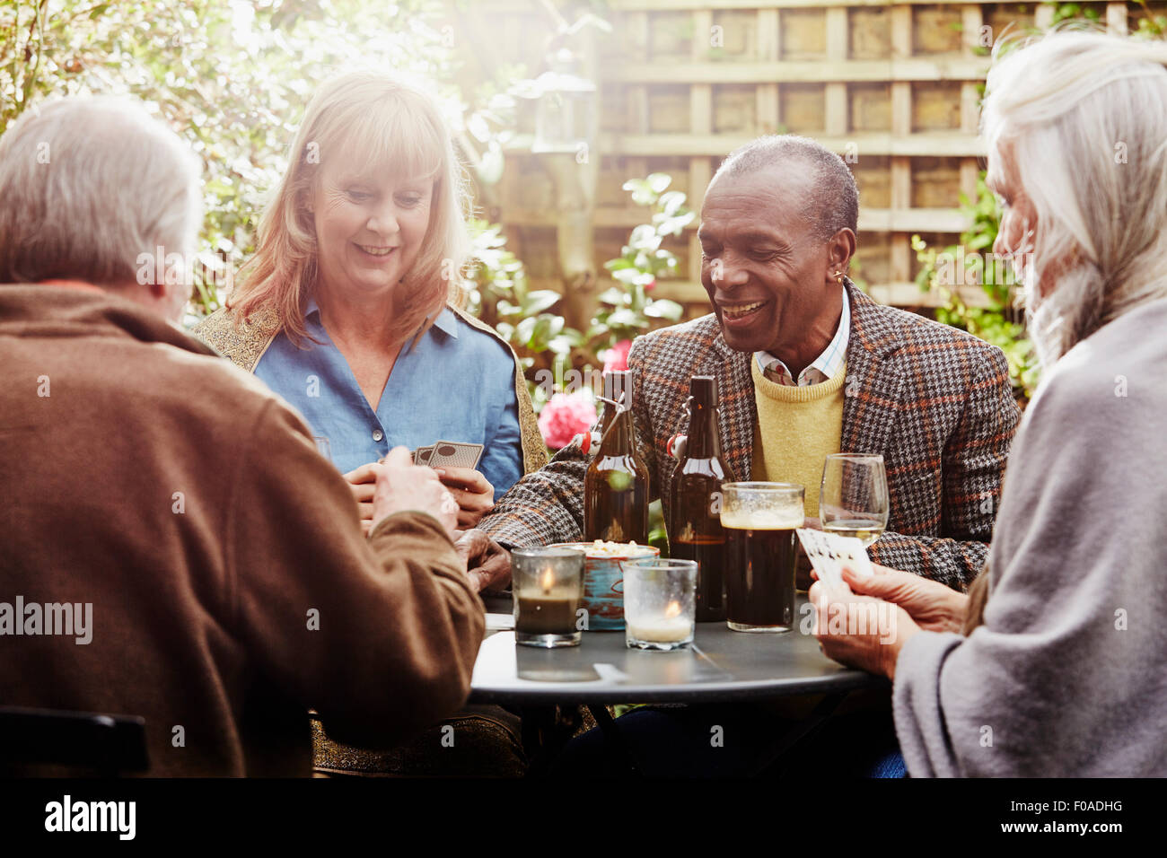 Senior friends drinking and playing cards in garden - Stock Image