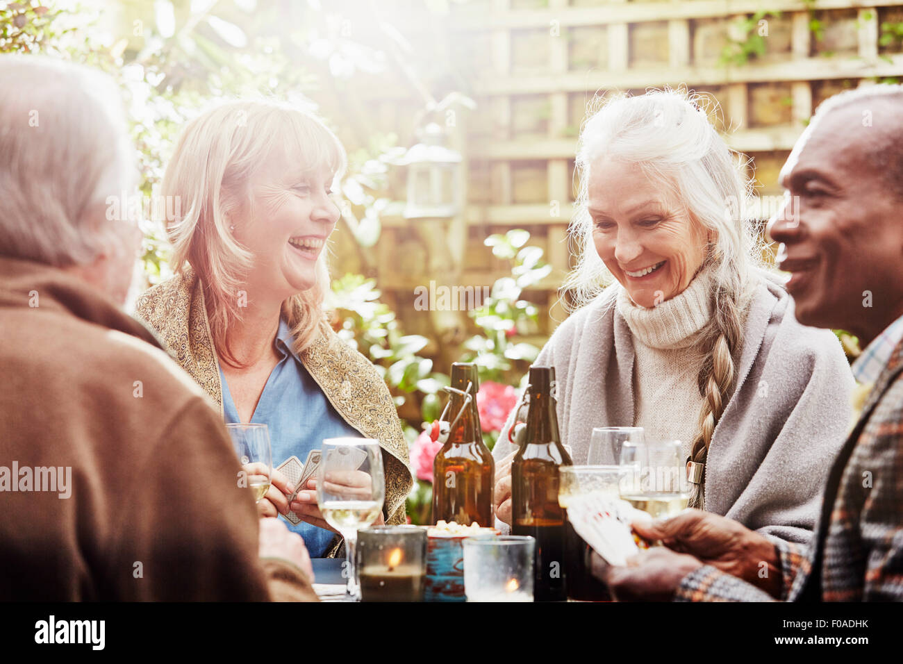 Senior friends playing cards in garden - Stock Image