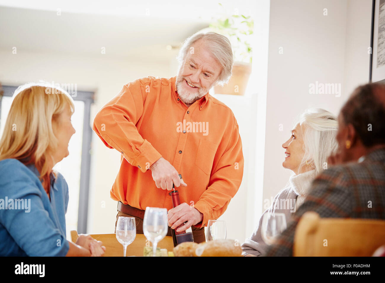 Senior man opening wine with friends - Stock Image