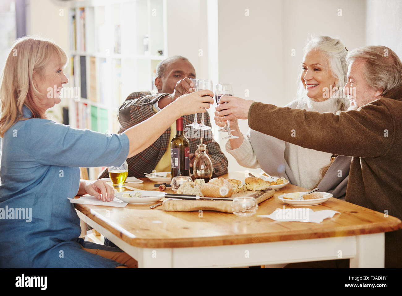 Senior friends making a toast at dinner table - Stock Image
