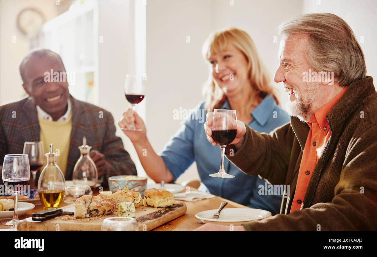 Senior friends making a toast at dinner - Stock Image
