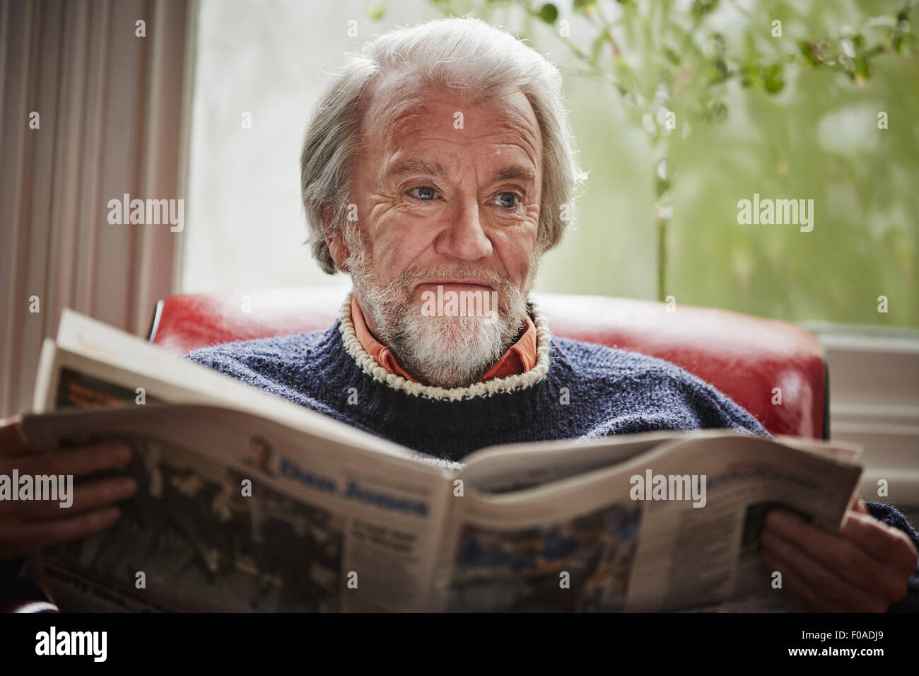 Senior man reading newspaper - Stock Image