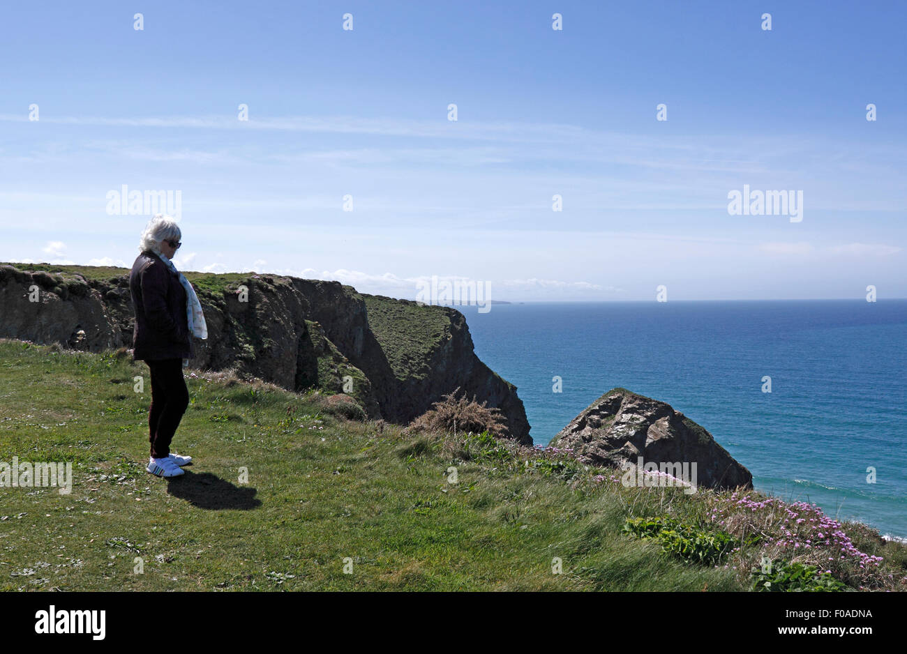 FEMALE STANDING ON A CLIFF EDGE. CORNWALL UK. - Stock Image