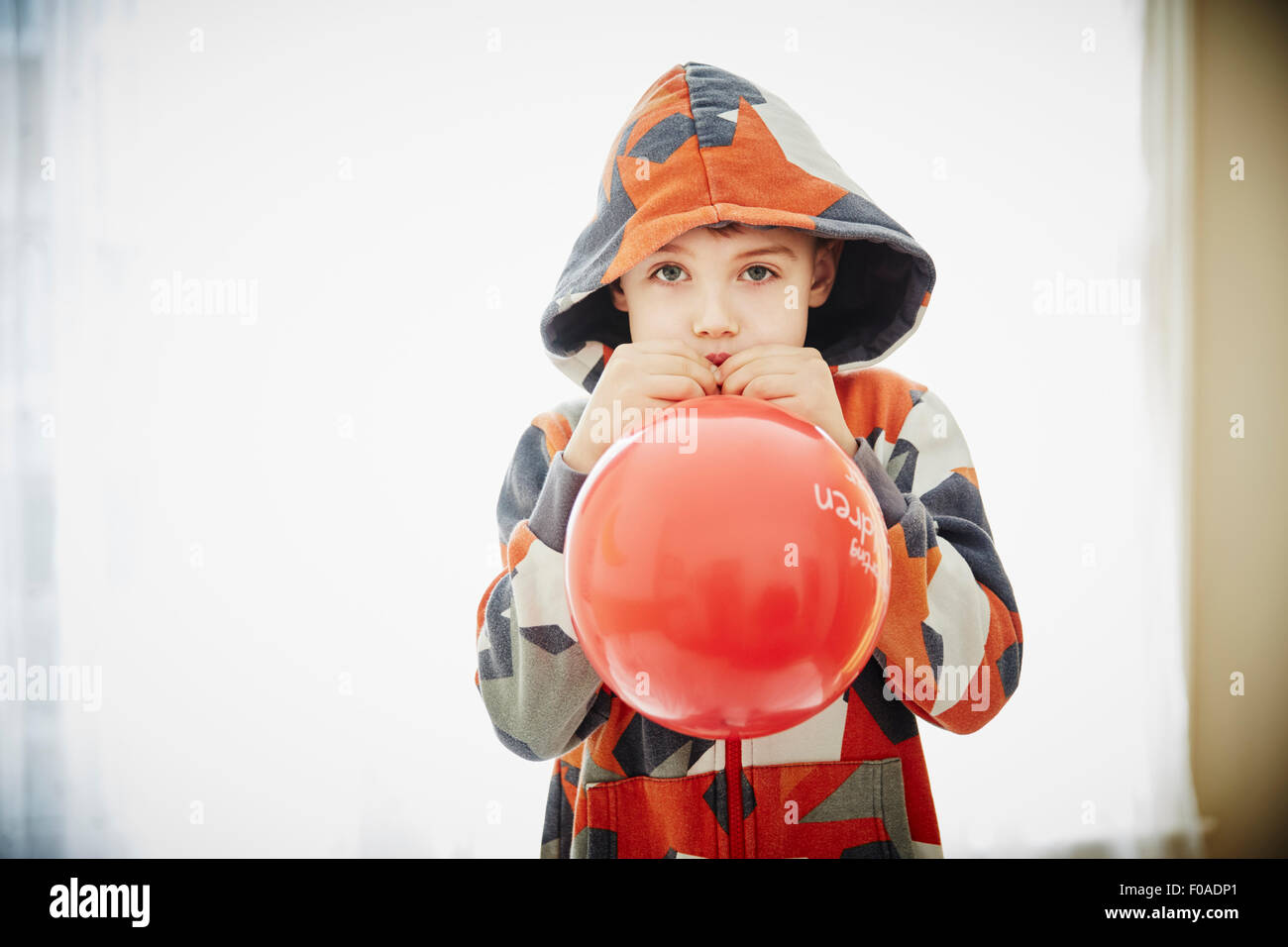 Young boy blowing red balloon - Stock Image