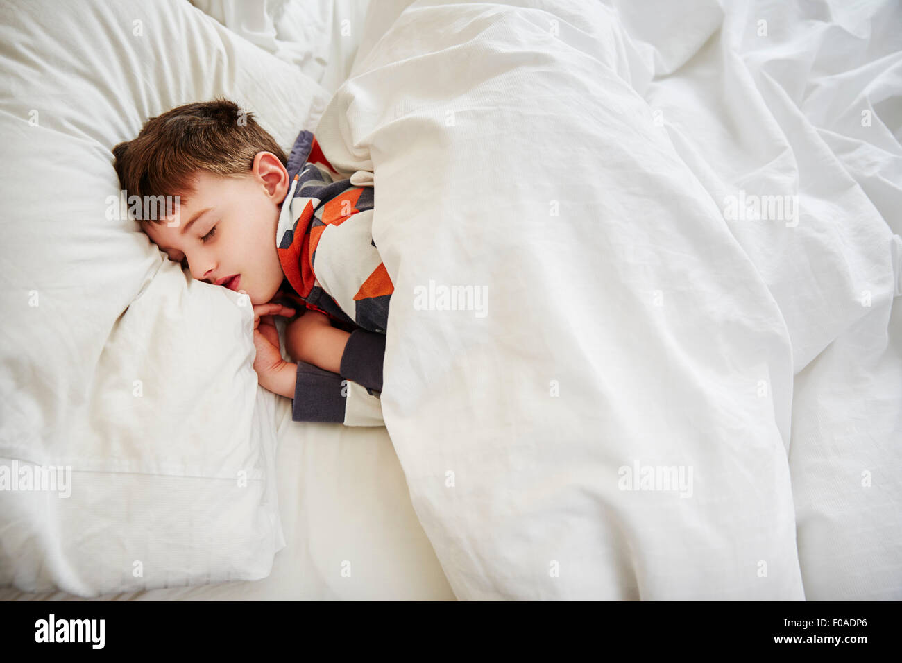 Young boy sleeping in bed - Stock Image