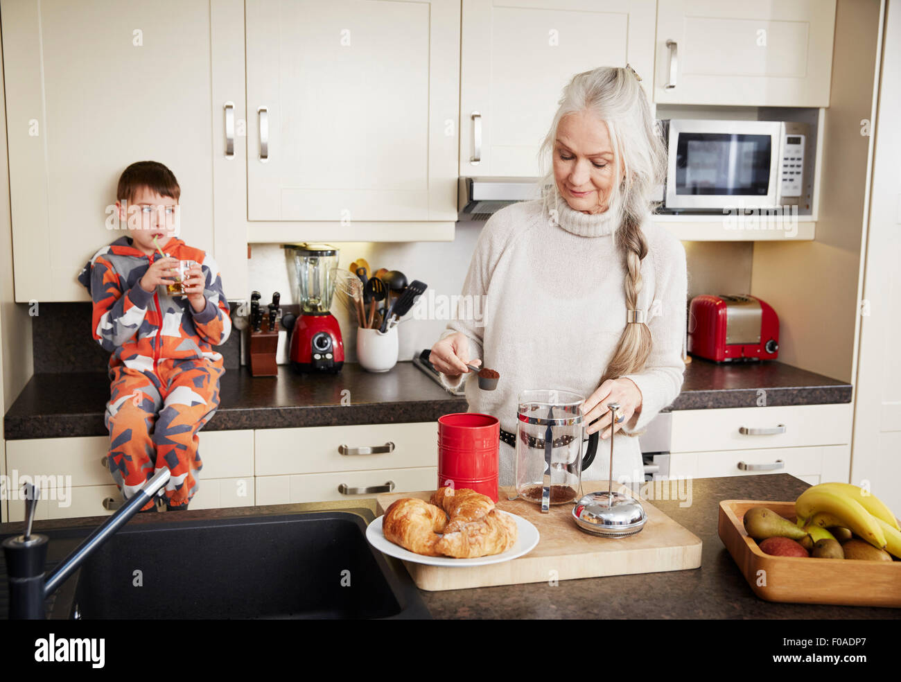 Grandmother making coffee, grandson sitting on kitchen counter - Stock Image