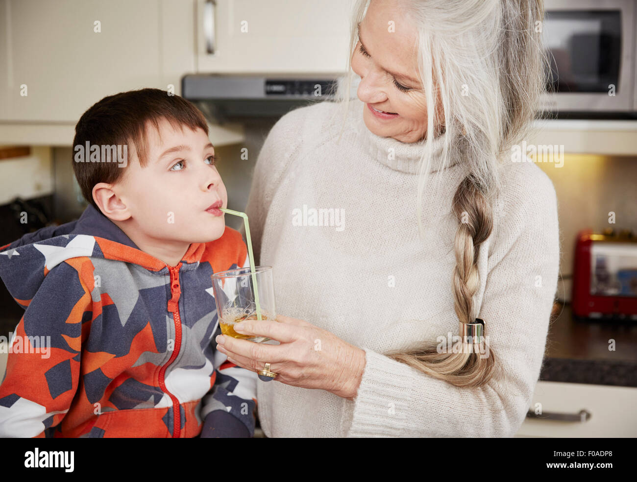 Grandmother offering grandson drink - Stock Image