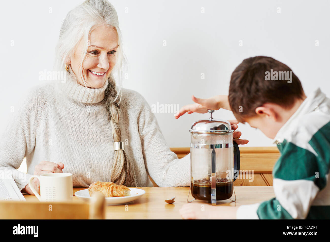 Grandmother and grandson making coffee in cafetiere - Stock Image