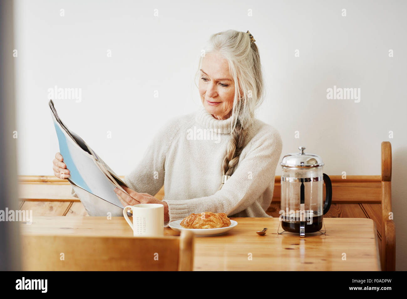 Senior woman reading newspaper at breakfast - Stock Image