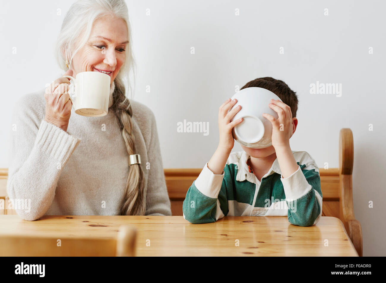 Boy drinking milk from bowl with grandmother - Stock Image