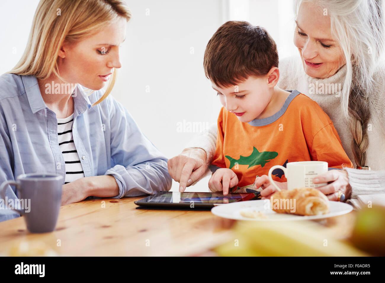 Three generation family using digital tablet - Stock Image