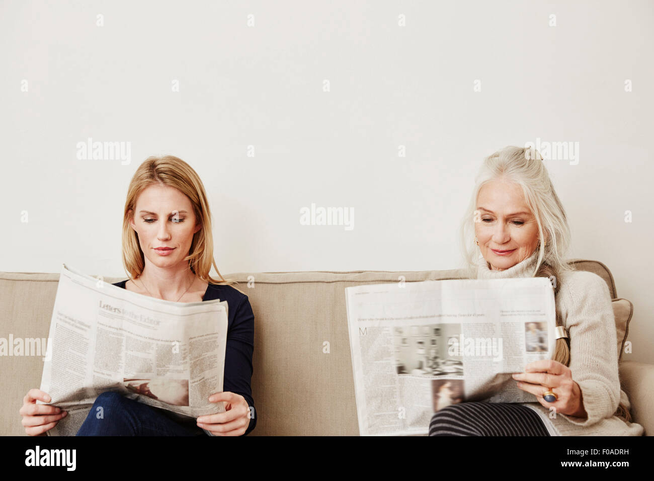 Senior and mid adult women reading newspapers - Stock Image