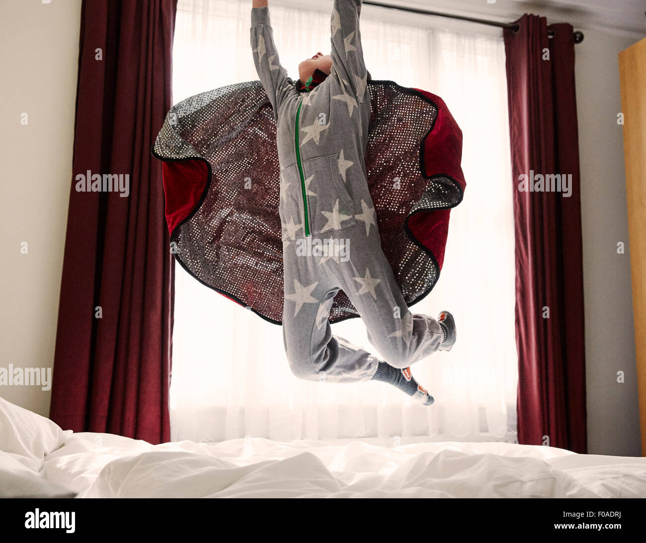 Young boy wearing cape jumping on bed - Stock Image
