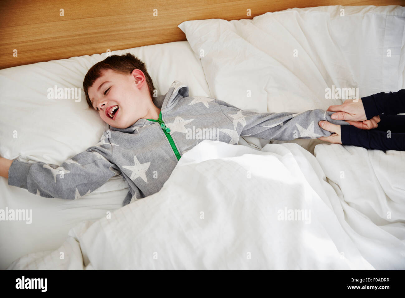 Mother pulling son out of bed - Stock Image