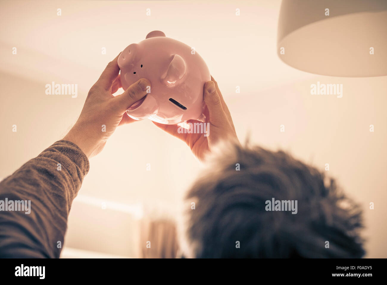 Man looking up at piggy bank - Stock Image