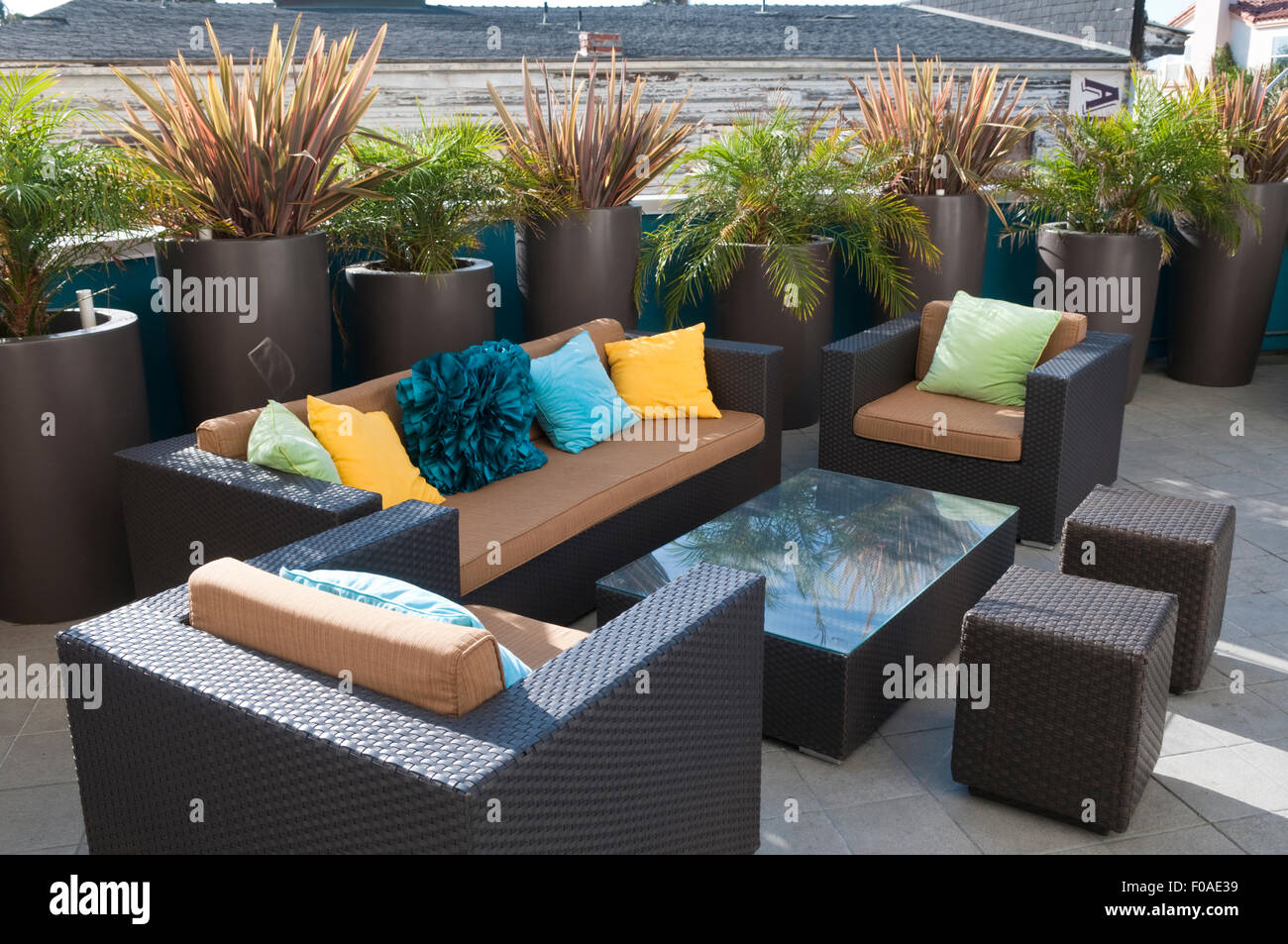 Stylish modern rattan patio furniture in dark brown with colorful cushions in a seating area surrounded by potted plants