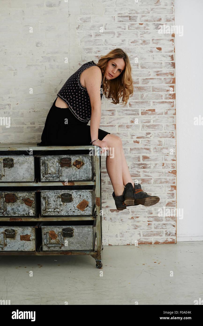 Mid adult woman sitting on metal dresser - Stock Image