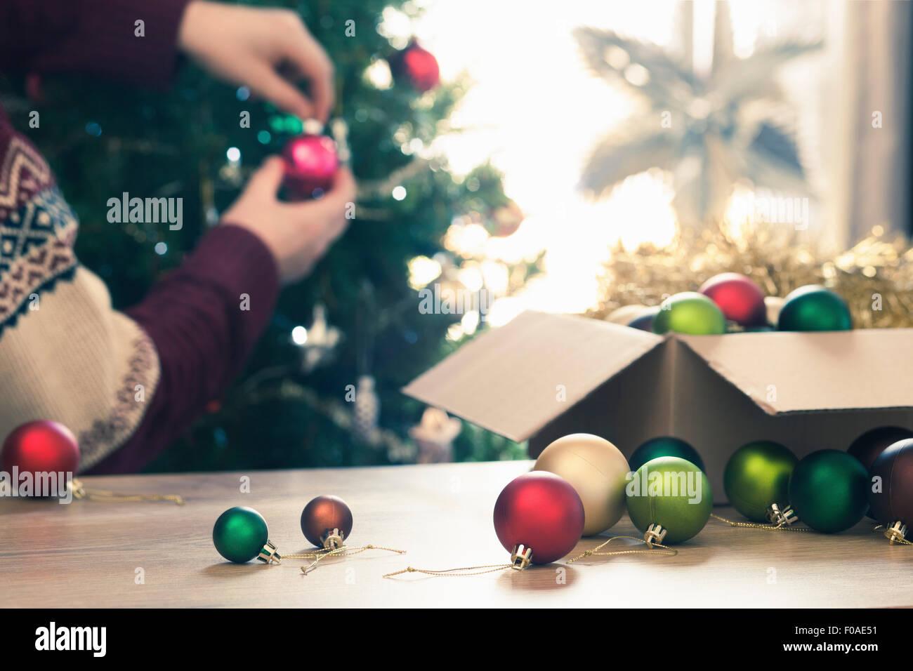 Person decorating christmas tree - Stock Image