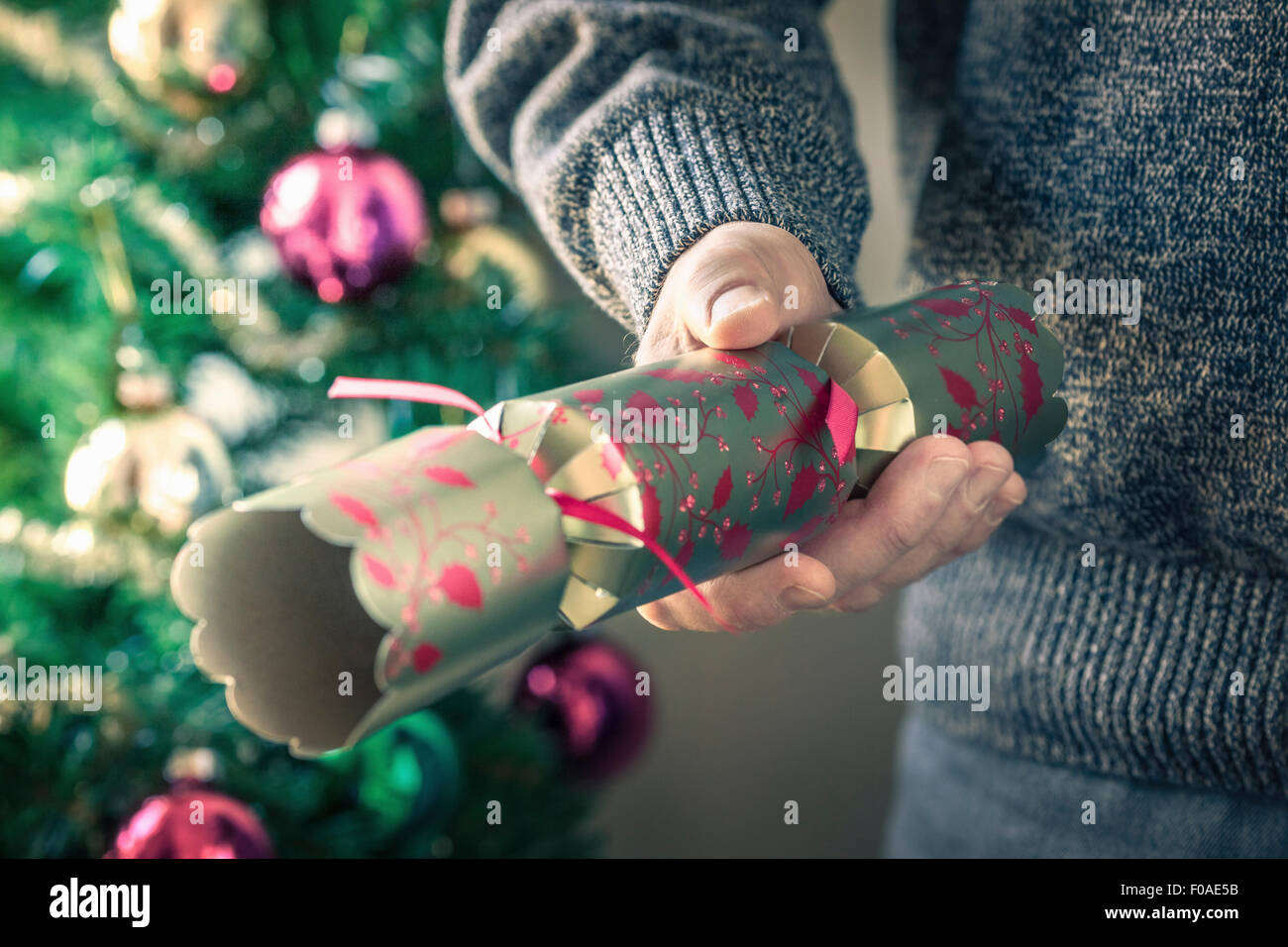 Person holding christmas cracker - Stock Image