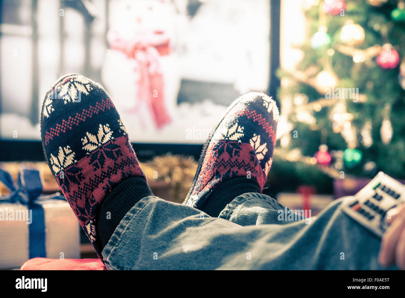 Person wearing slippers with feet up Stock Photo