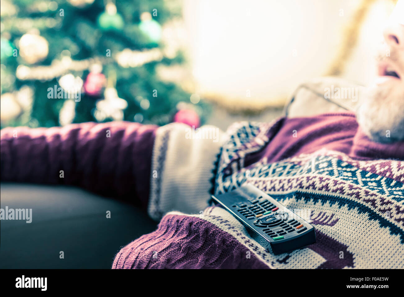 Man wearing sweater asleep with remote control on chest - Stock Image