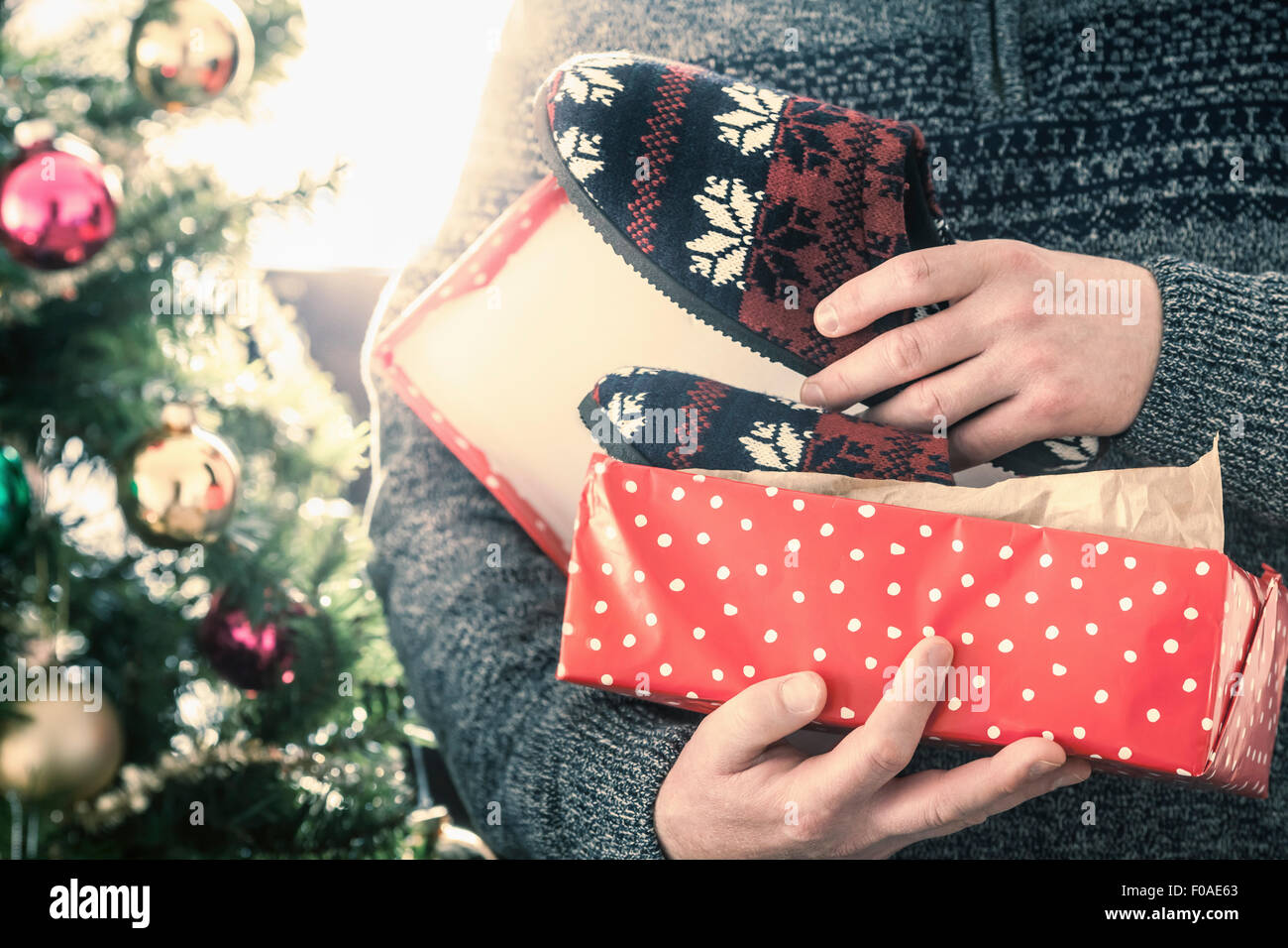 Person opening pair of slippers - Stock Image