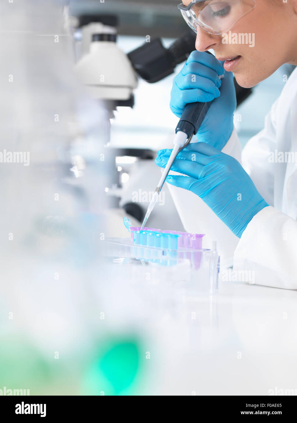Female scientist pipetting sample into a vial for analytical testing in a laboratory - Stock Image