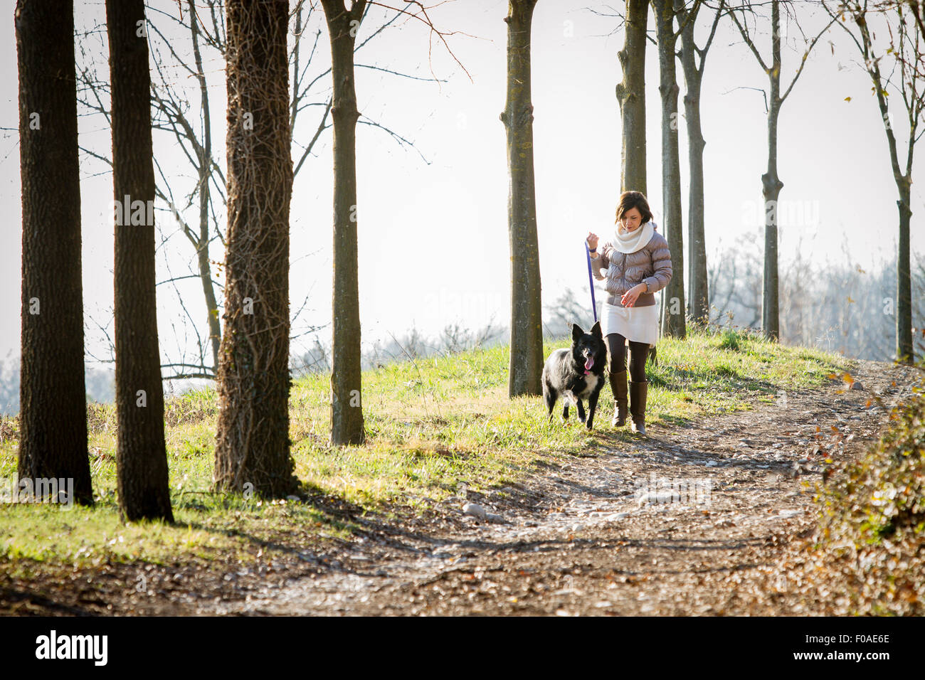 Mid adult woman walking her dog on dirt path - Stock Image