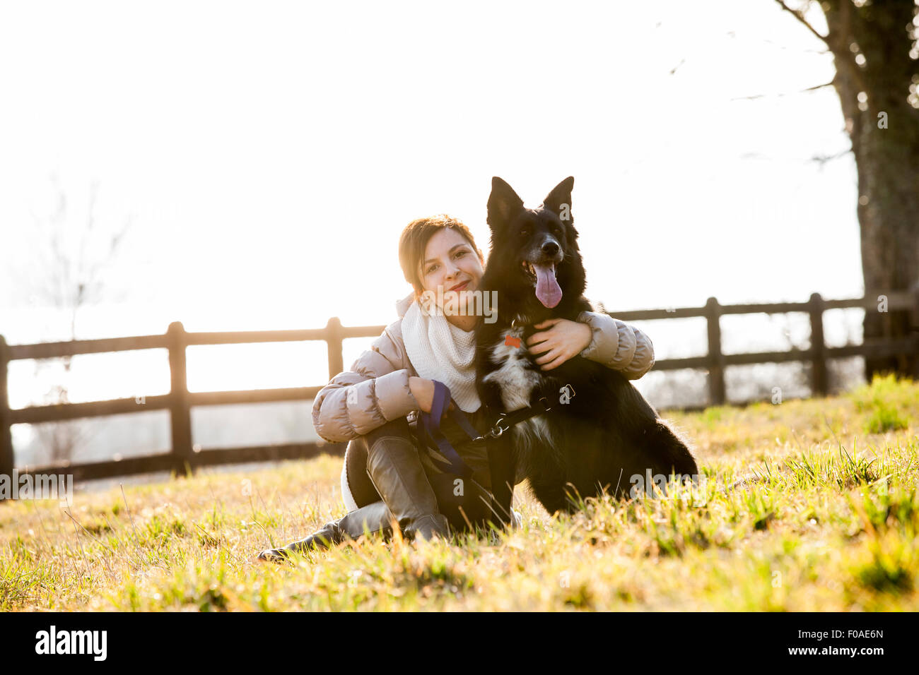 Portrait of mid adult woman sitting with her dog in field - Stock Image