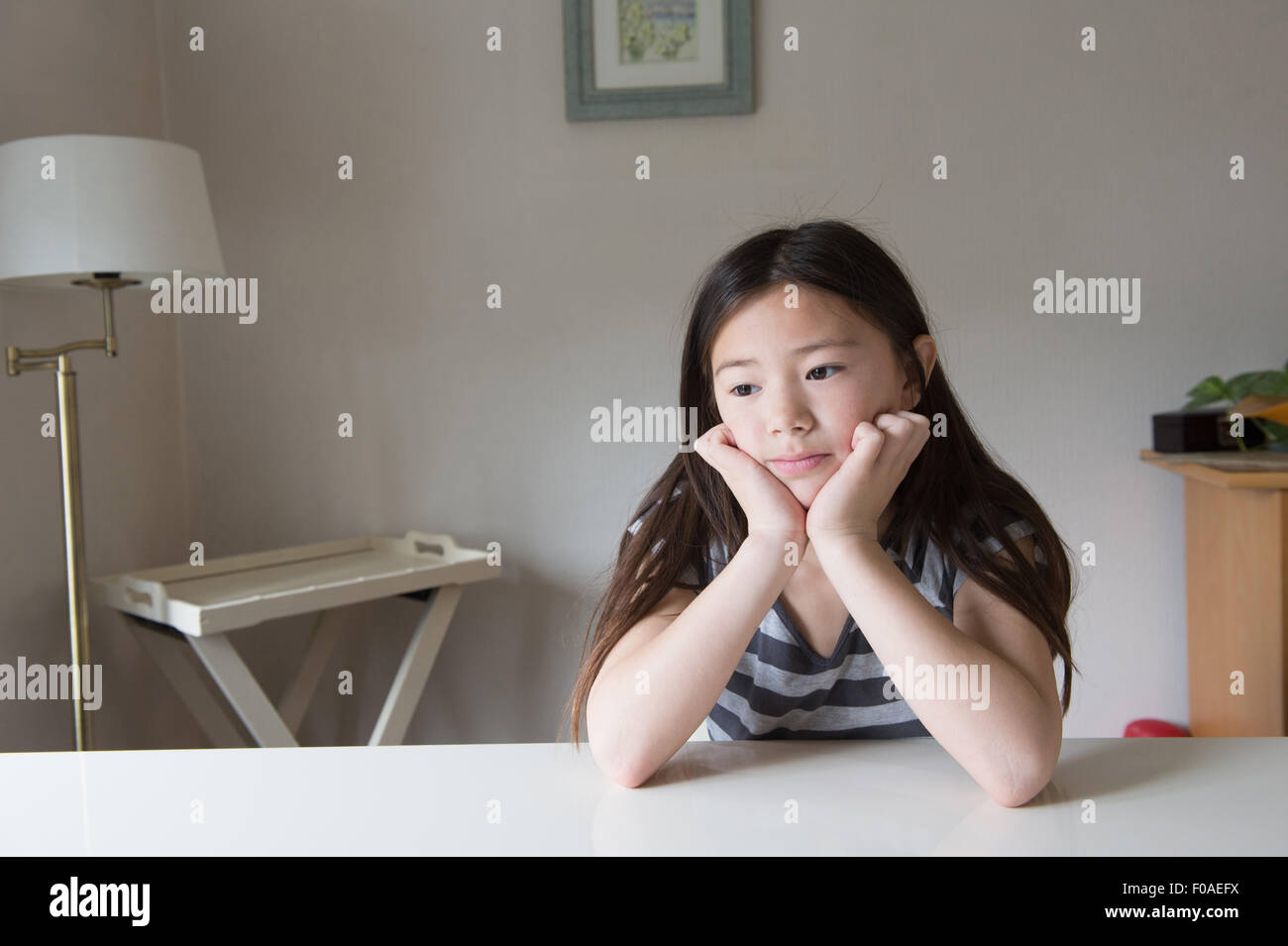 Fed up girl at table with chin in hands - Stock Image