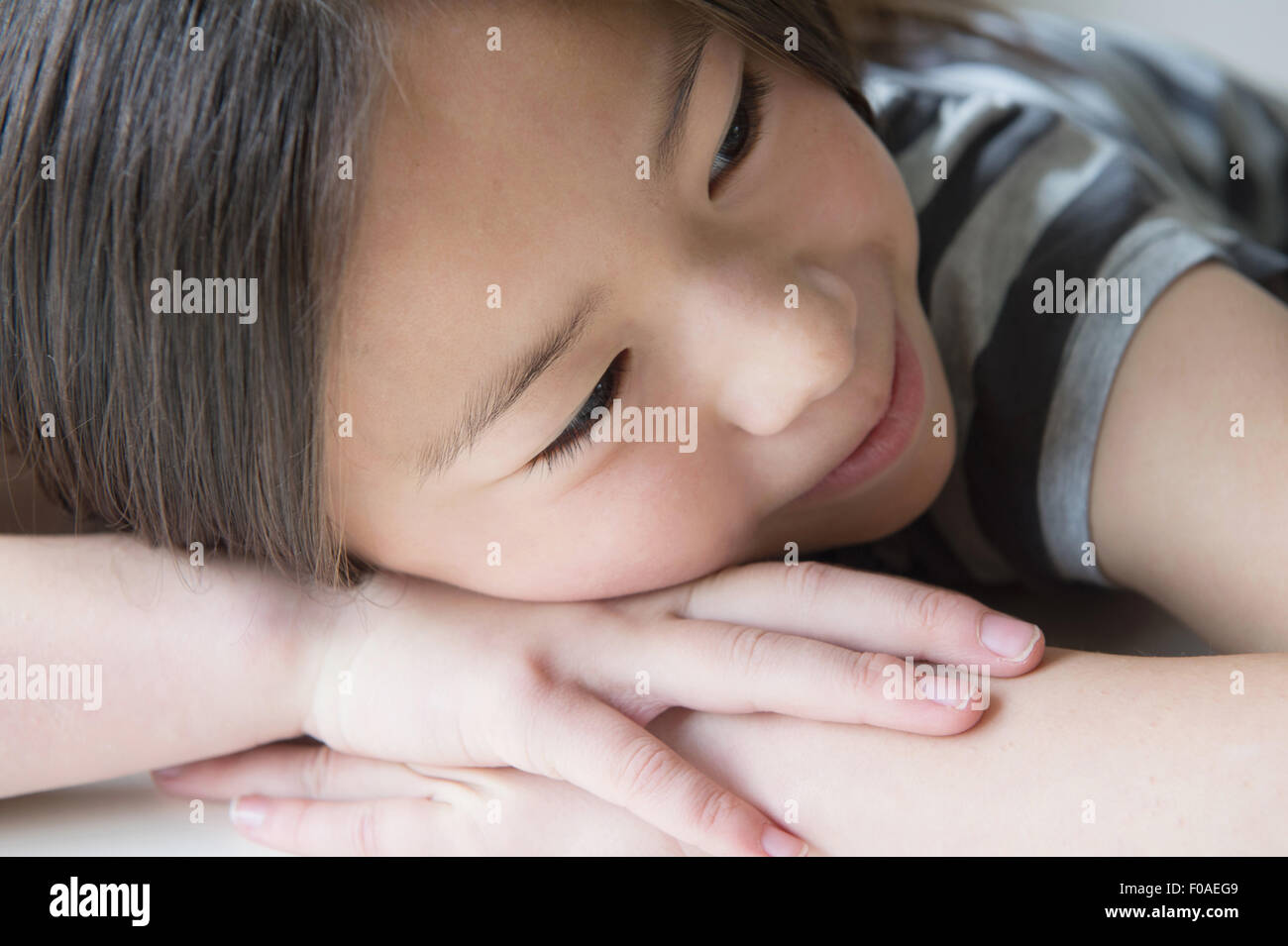 Close up of girl resting on hands - Stock Image