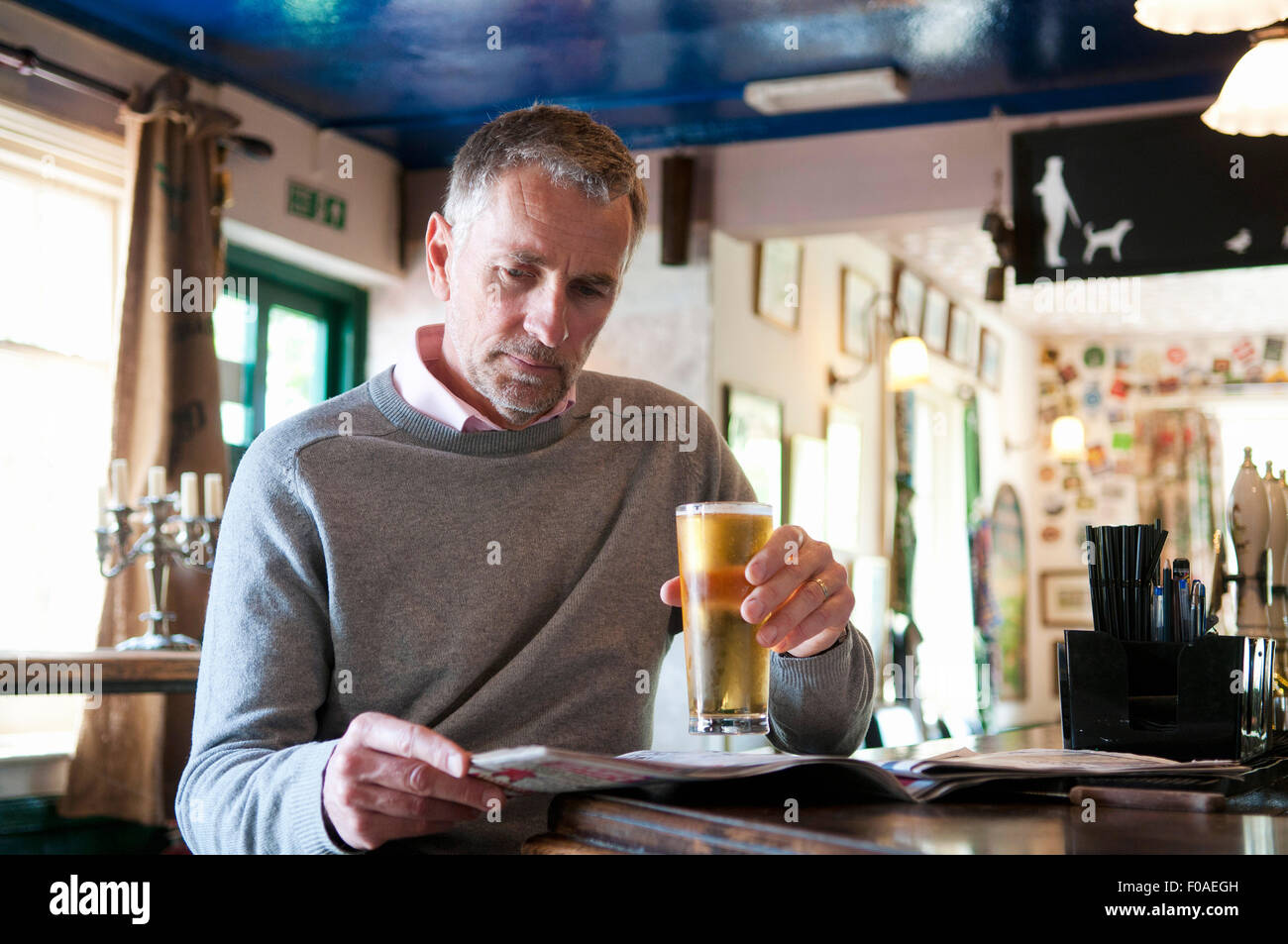 Mature man drinking beer and reading newspaper in pub - Stock Image