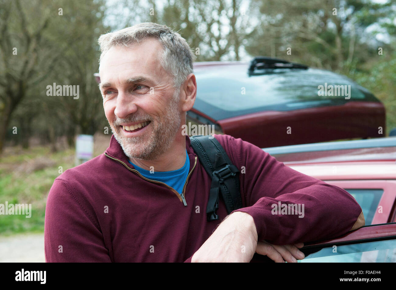 Portrait of male hiker leaning against car door - Stock Image
