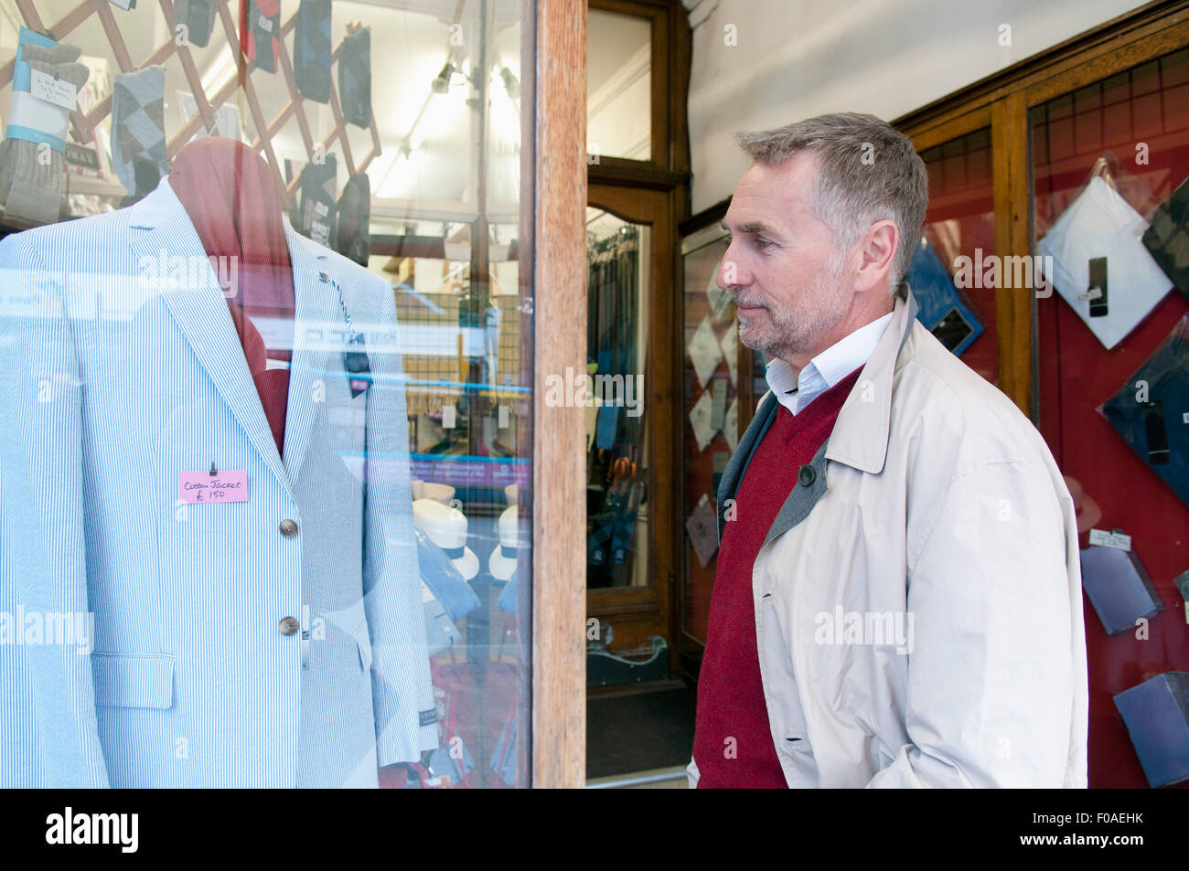 Mature man looking at suit jacket in tailors shop window - Stock Image