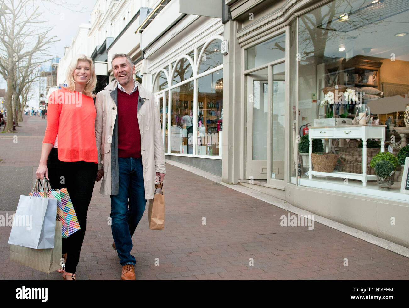 Couple carrying shopping bags on village street - Stock Image