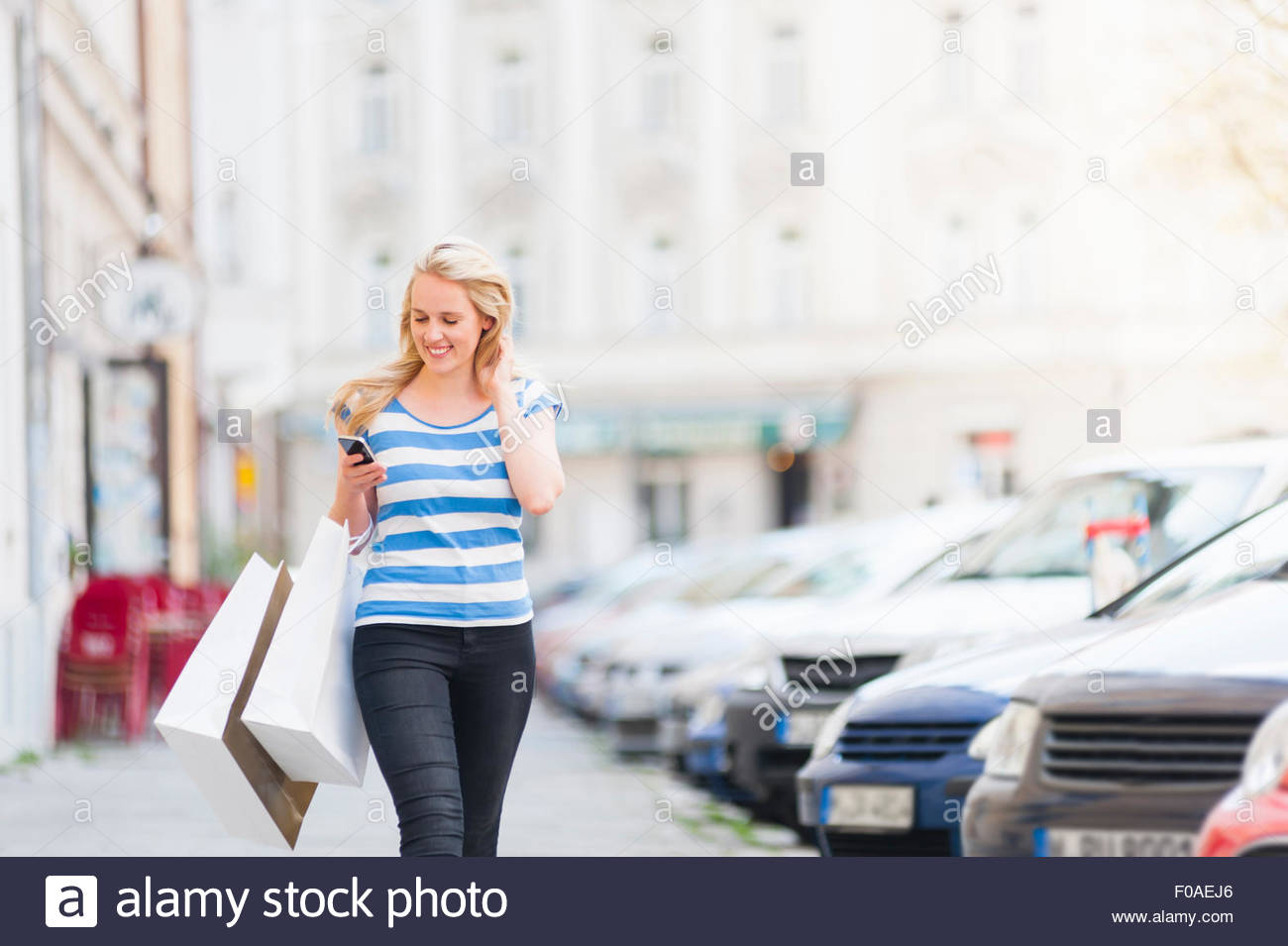 Young woman walking down street, carrying shopping bags, using smartphone - Stock Image