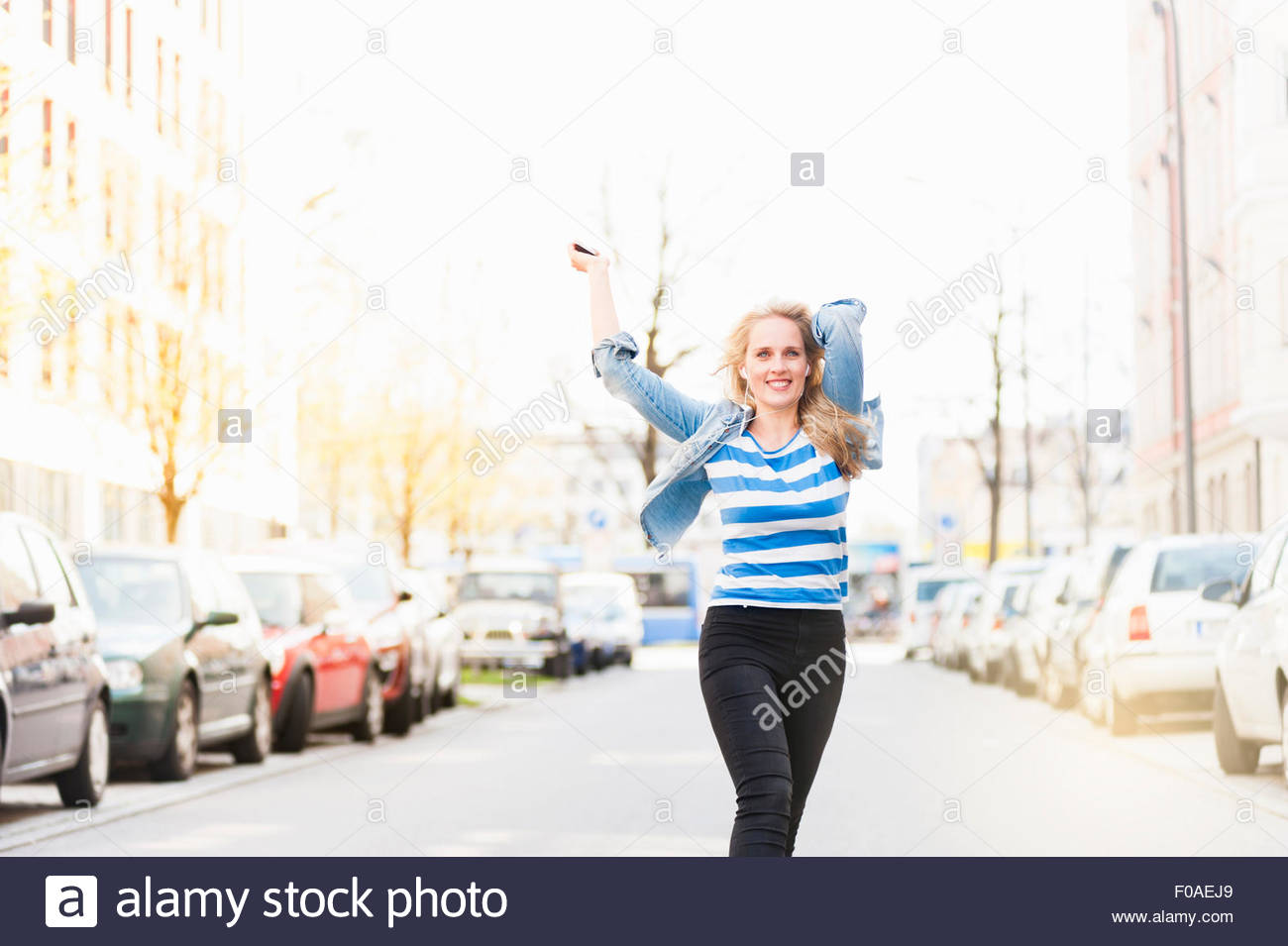 Excited young woman, dancing along street - Stock Image