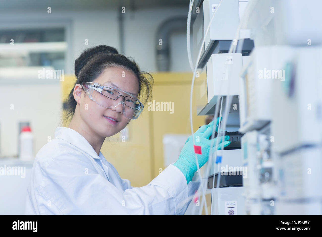 Portrait of young female scientist  using scientific equipment in lab - Stock Image