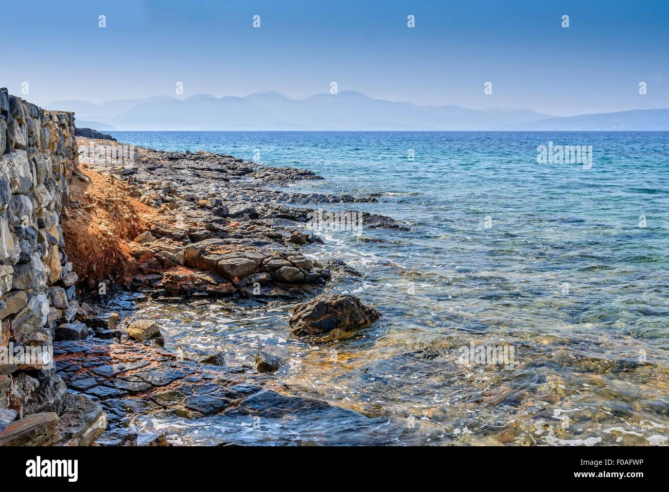 Sea lapping against rocks with a stone wall in the foreground and hills in the distance. - Stock Image