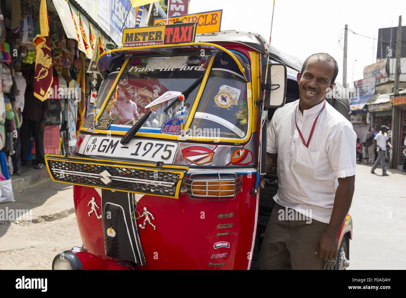Portrait of driver standing besides tuk tuk, Colombo, Sri Lanka - Stock Image