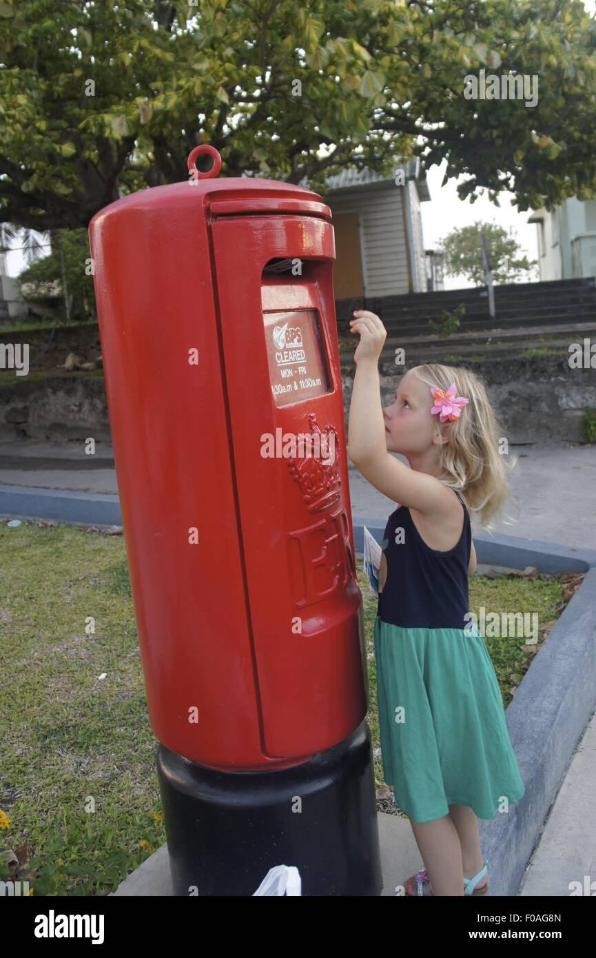 Blonde girl posting letter in postbox at Lesser Antilles, Caribbean island, Barbados - Stock Image